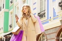 Stilfullt härligt blont hår som ler flickan med shopping genom att använda hennes telefon lycklig shopping Royaltyfri Bild