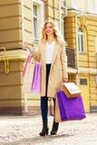 Stilfullt härligt blont hår som ler flickan med shopping lycklig shopping Fotografering för Bildbyråer