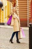 Stilfullt härligt blont hår som ler flickan med shopping lycklig shopping Royaltyfria Bilder
