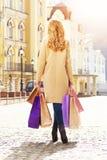 Stilfullt härligt blont hår som ler flickan med shopping lycklig shopping Royaltyfri Foto