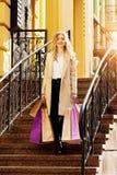 Stilfullt härligt blont hår som ler flickan med shopping lycklig shopping Arkivfoton