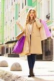 Stilfullt härligt blont hår som ler flickan med shopping lycklig shopping Royaltyfri Bild