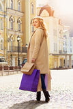 Stilfullt härligt blont hår som ler flickan med shopping lycklig shopping Royaltyfria Foton