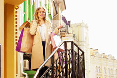 Stilfullt härligt blont hår som ler flickan med shopping lycklig shopping Arkivbild