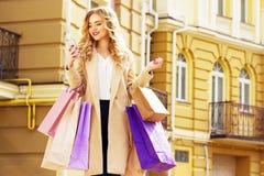 Stilfullt härligt blont hår som ler flickan med shopping och använder hennes telefon lycklig shopping Royaltyfria Foton