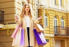 Stilfullt härligt blont hår som ler flickan med shopping och telefonen i henne händer lycklig shopping Royaltyfria Foton