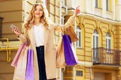 Stilfullt härligt blont hår som ler flickan med shopping som kallar taxien lycklig shopping Arkivfoton