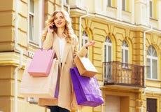 Stilfullt härligt blont hår som ler flickan med shopping som talar telefonen lycklig shopping Fotografering för Bildbyråer