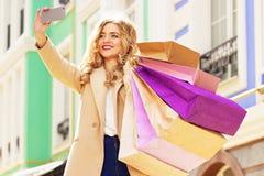 Stilfullt härligt blont hår som ler flickan med shopping som tar selfie på hennes telefon lycklig shopping Fotografering för Bildbyråer