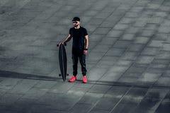 Stilfullt hipstermananseende med en longboard på konkreta tegelplattor Arkivfoton