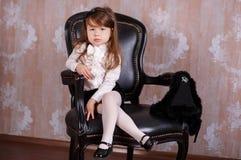 Stilfullt klätt för ung flicka för brunettdockadam som ett framstickande i den vita officiella skjortasvartkjolen som poserar sam Royaltyfri Foto