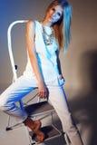 Stilfullt modefoto av den härliga slanka modellen i en vit dräkt med halsbandet och rakt blont hår som poserar i studion Royaltyfri Fotografi