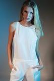 Stilfullt modefoto av den härliga slanka modellen i en vit dräkt med rakt blont hår Royaltyfria Bilder