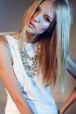 Stilfullt modefoto av den härliga slanka modellståenden i en vit dräkt med rakt blont hår Royaltyfri Foto