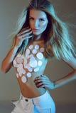 Stilfullt modefoto av den sexiga slanka blonda modellen i vit byxa med kropp-konst Arkivfoton