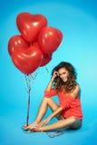 Stilfullt och att le, härlig kvinna med ballonger över blå bakgrund Fotografering för Bildbyråer