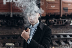 Stilfullt röka för gangsterman posera på bakgrund av järnvägen E Arkivfoton