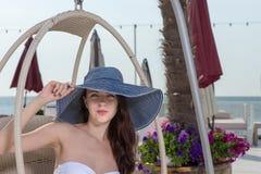 Stilfullt sammanträde för ung kvinna på en badort royaltyfria foton