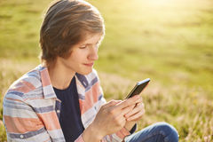Stilfullt tonåringsammanträde på gröna garss som rymmer utomhus den smarta telefonen i hans händer som skriver meddelanden eller  Fotografering för Bildbyråer
