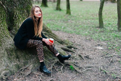 Stilfullt ung flickasammanträde nära trädet i vår parkerar fotografering för bildbyråer