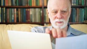 Stilig äldre hög man som hemma arbetar på bärbar datordatoren Fjärrkontrollfrilansarbete på avgång arkivfilmer