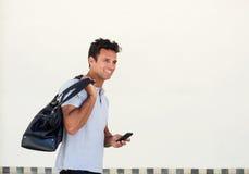 Stilig äldre man som går med påsen och mobiltelefonen arkivbilder