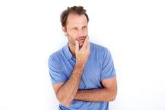 Stilig äldre man som tänker med handen på hakan fotografering för bildbyråer