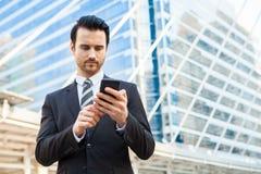 Stilig affärsman i den formella dräkten som ser smart telefonstenras Fotografering för Bildbyråer