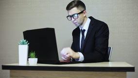 Stilig affärsman i dräkt- och exponeringsglasarbete på en bärbar dator, skärmreflexion stock video