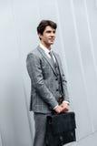 Stilig affärsman i dräktanseende med portföljen Royaltyfri Bild