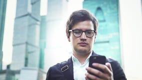 Stilig affärsman i dräkten som nallar över hans stad för smartphoneskärmMoskva stock video