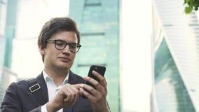 Stilig affärsman i exponeringsglas som nallar över hans stad för smartphoneskärmMoskva lager videofilmer