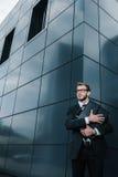 Stilig affärsman i glasögon som kramar portföljen och bort ser Arkivfoton