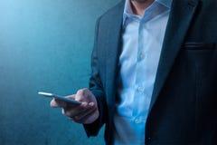 Stilig affärsman i modern affärsdräkt genom att använda mobiltelefonen Royaltyfri Bild