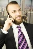 Stilig affärsman med att le för skägg som är lyckligt på telefonen fotografering för bildbyråer