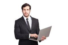 Stilig affärsman med en bärbar dator royaltyfria bilder