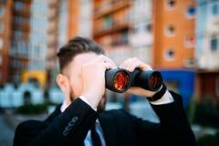 Stilig affärsman med kikare som utomhus spionerar på konkurrenter royaltyfri bild