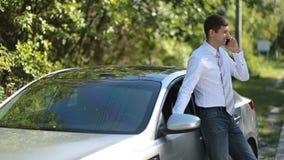 Stilig affärsman som använder mobiltelefonen nära bilen arkivfilmer