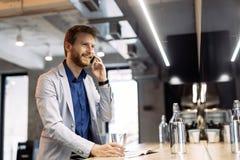 Stilig affärsman som använder smartphonen i bar arkivfoton