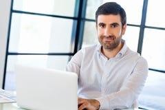 Stilig affärsman som arbetar på datoren arkivbild