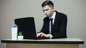 Stilig affärsman som arbetar på kontoret som skriver på en bärbar dator stock video