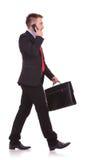 Stilig affärsman som går på studiobackgound Arkivfoto