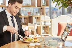 Stilig affärsman som har lunch Arkivfoto