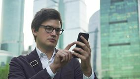 Stilig affärsman som nallar över hans smartphoneskärm i Moskvastad stock video