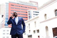 Stilig affärsman som talar på mobiltelefonen i staden royaltyfri fotografi
