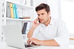 Stilig affärsman som använder bärbar datordatoren och talar på telefonen Arkivfoton