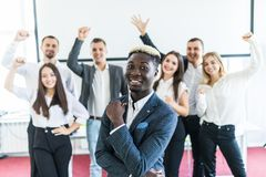 Stilig afrikansk affärsman framme av gruppen av att fira businesspeople på bakgrund arkivbild