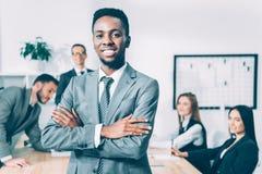 stilig afrikansk amerikanchef med korsade armar med suddiga mångkulturella kollegor royaltyfri fotografi