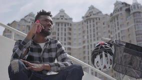 Stilig afrikansk amerikanman f?r st?ende som sitter n?ra hans cykel p? bakgrunden av stads- arkitektur Grabbsamtalet arkivfilmer