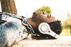 Stilig afrikansk amerikanman f?r st?ende och lycklig ung man med musikh?rlurargatan royaltyfri fotografi
